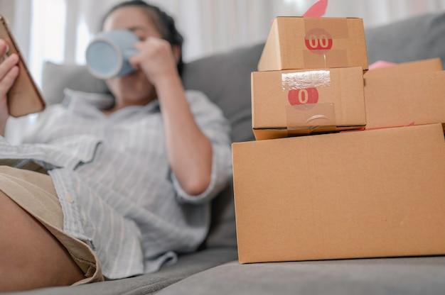 Femme asiatique propriétaire d'entreprise travaillant à domicile avec des boîtes d'emballage au travail, elle boit de l'eau