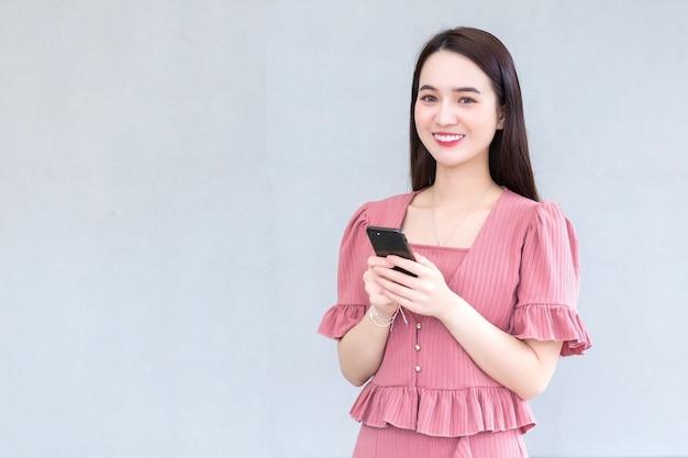 Une femme asiatique qui a les cheveux longs et porte une robe rose tient un smartphone dans les mains et sourit