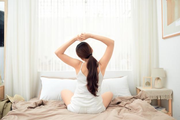 Femme asiatique qui s'étend dans son lit après le réveil, vue arrière