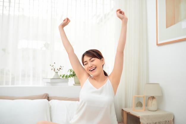 Femme asiatique qui s'étend dans son lit après le réveil