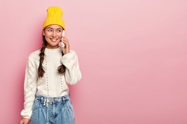 Une femme asiatique ravie parle via un téléphone intelligent, a une conversation agréable, appelle un ami, porte un pull et un jean blanc chaud, regarde de côté avec le sourire, pose sur un mur rose