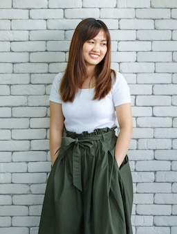 Une femme asiatique ravie portant des vêtements à la mode debout avec les mains dans les poches et regardant à l'extérieur sur fond de mur de briques blanches