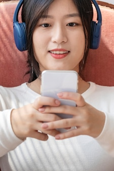 Femme asiatique regardant un clip vidéo depuis le téléphone