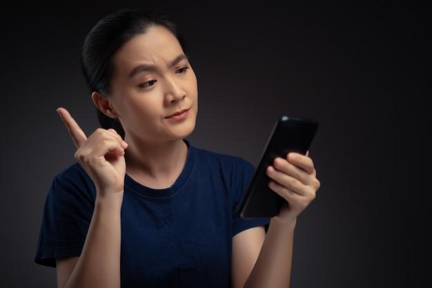 Femme asiatique regardant les nouvelles de lecture de smartphone et se sentir confus.