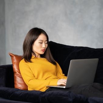 Femme asiatique regardant un ordinateur portable, travaillant à la maison, couchée sur le canapé. femme japonaise malheureuse et bouleversée