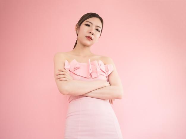 Femme asiatique regarde vers le bas et bras croisés, belles femmes posant sur fond rose.