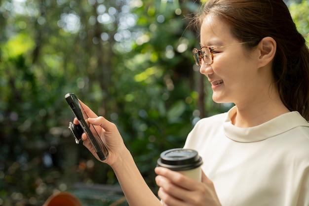 Femme asiatique, regarder, téléphone portable, à, jardin