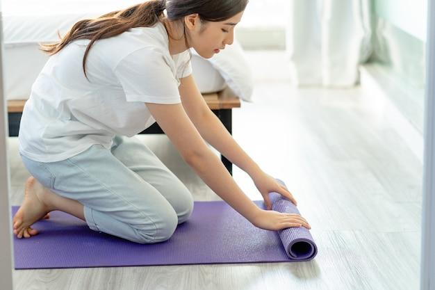 Femme asiatique répandant un tapis de yoga pour préparer le yoga à la maison