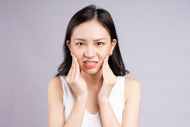 Une femme asiatique ressent de la douleur à cause des dents de sagesse
