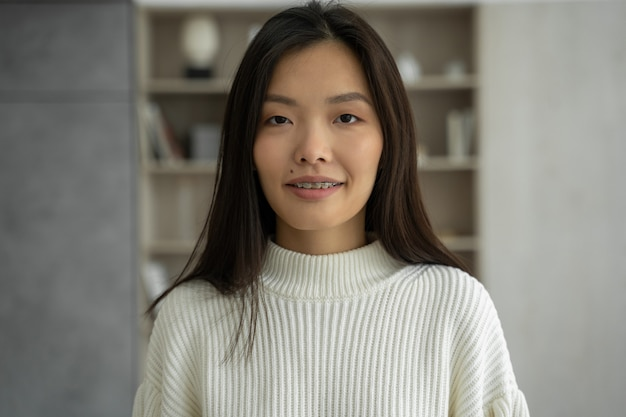 Une femme asiatique ressent des sourires heureux et regarde la caméra debout dans son salon