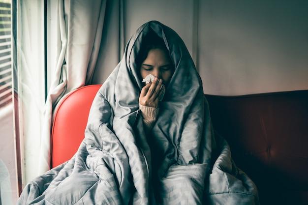 Une femme asiatique a un rhume, utilise un mouchoir pour se couvrir la bouche lorsqu'elle tousse et éternue à la maison, empêchant la propagation du virus covid 19, concept de soins de santé. mise au point sélective et douce.