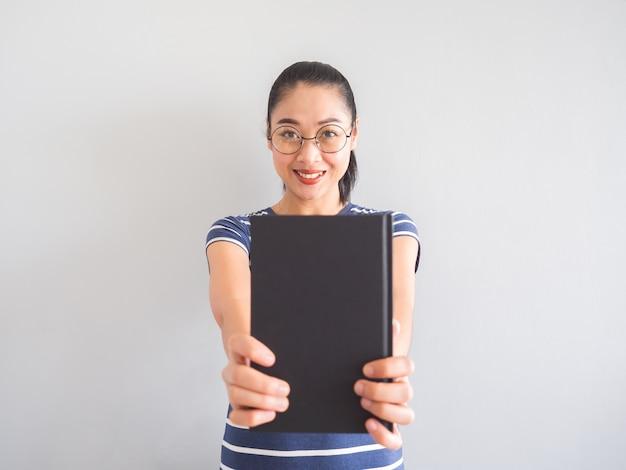 Une femme asiatique ringarde sourit et tient un bon livre.