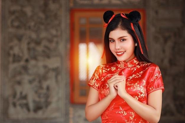 Femme asiatique en robe chinoise rouge cheongsam qipao traditionnel avec un geste de félicitation et de sourire heureux