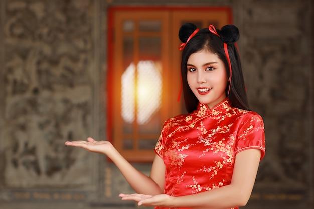 Femme asiatique en robe chinoise rouge traditionnelle cheongsam qipao avec le geste d'introduire ou de montrer quelque chose avec un visage souriant heureux