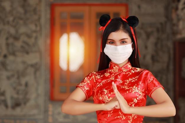 Femme asiatique en robe chinoise rouge traditionnelle cheongsam qipao porter un masque de protection pour les soins de santé avec un geste de félicitation