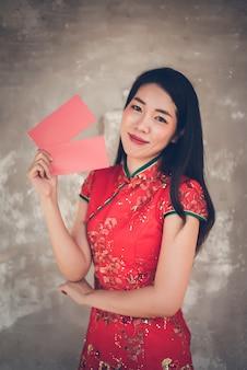 Femme asiatique en robe rouge traditionnelle cheongsam au nouvel an chinois