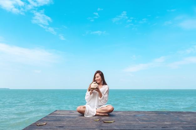 Femme asiatique s'asseoir au bord de la mer