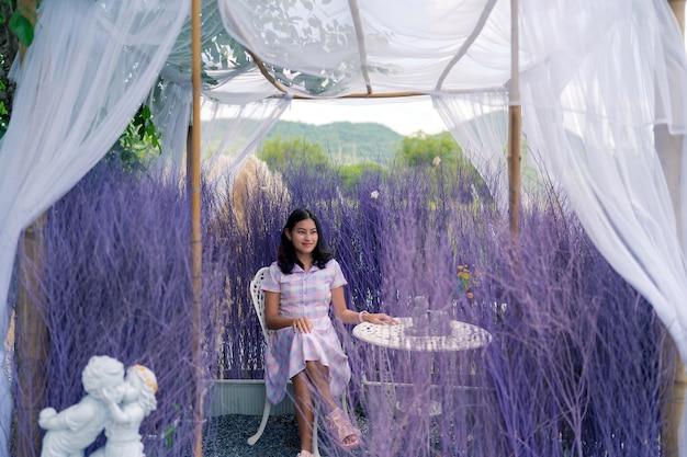 Une femme asiatique s'assoit à une table blanche dans un jardin décoré d'herbe sèche violette et d'un rideau blanc romantique, une fille heureuse se détend en vacances en regardant la vue sur la nature