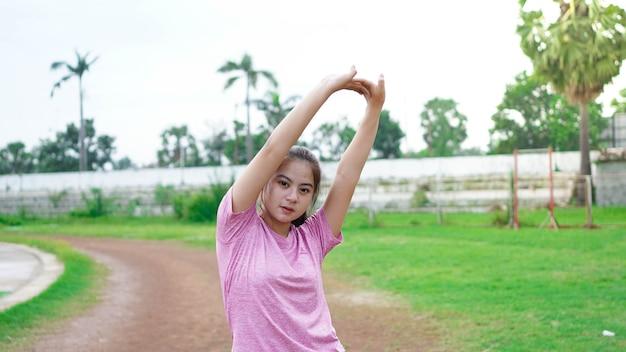 Femme asiatique s'échauffant avant de courir