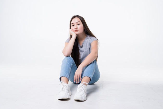 Femme asiatique s'ennuie assis sur le sol isolé sur un mur blanc.