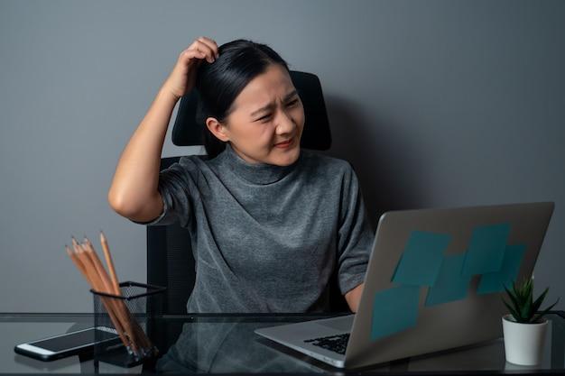 Femme asiatique s'ennuie et ennuyé, se gratte la tête, travaillant sur un ordinateur portable au bureau