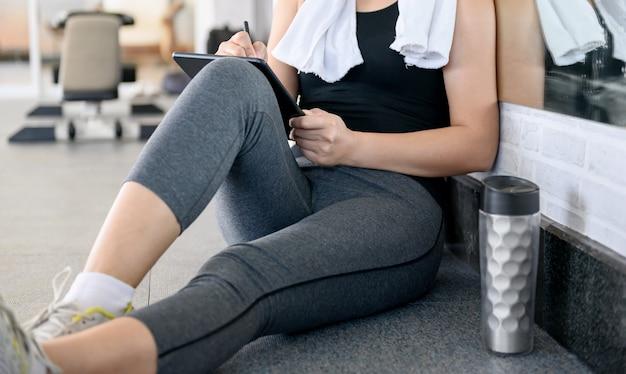 Femme asiatique s'entraînant et travaillant seule en ligne au gym.