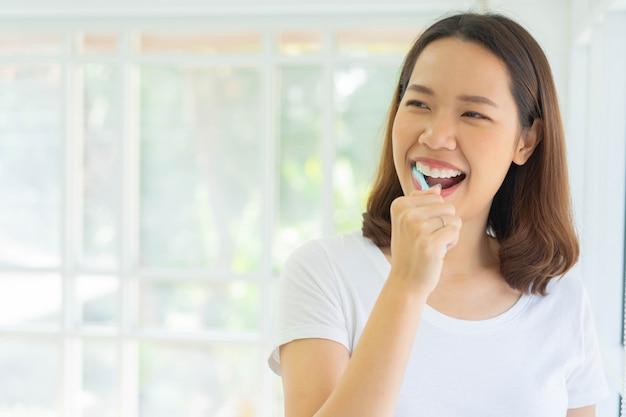 Femme asiatique se brosser les dents à la salle de bain le matin pour le concept de vie saine et routinière