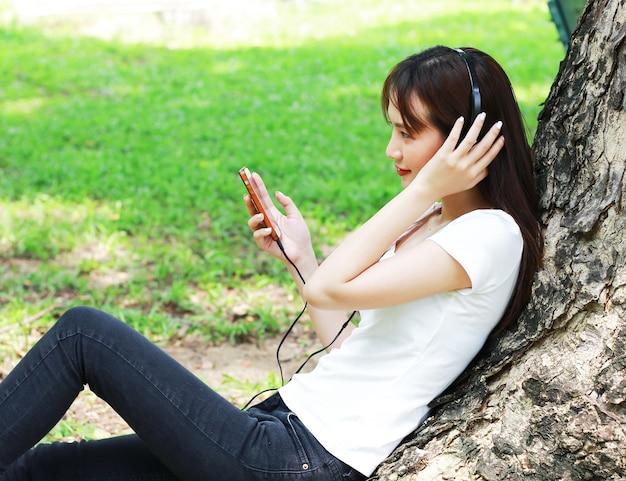 Femme asiatique se détendre en écoutant de la musique sur les smartphones joyeusement dans le parc.