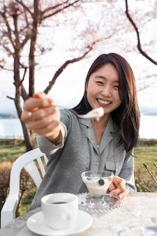 Femme asiatique se détendre à l'extérieur à côté d'un cerisier