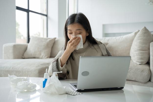Une femme asiatique se mouche dans une serviette assise à un bureau à domicile étudie sur un ordinateur portable un malade