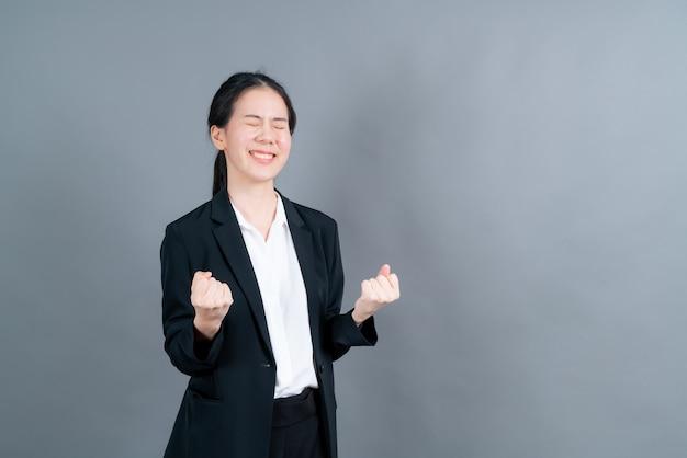 Femme asiatique se réjouissant de son succès et de sa victoire en serrant les poings de joie. femme chanceuse étant heureuse d'atteindre son but et ses objectifs. émotions positives, sentiments