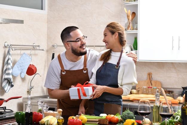 Femme asiatique se sentir heureuse lorsqu'elle est surprise par un cadeau de petit ami tout en cuisinant dans la cuisine et en préparant des aliments sains ensemble