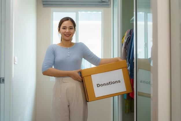 Une femme asiatique se tient près d'un placard de vêtements dans le vestiaire, portant une boîte de vêtements donnée à apporter au centre de dons.