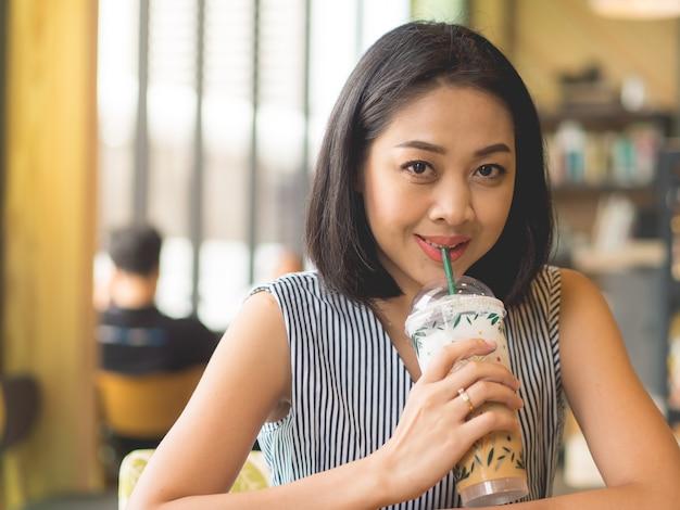 Femme asiatique se trouve au café café avec café glacé sur la table.