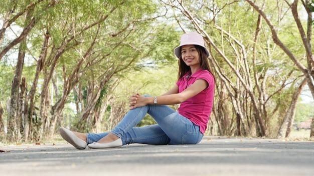 Femme asiatique, séance, sur, arbre, tunnel, route