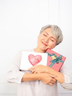 Femme asiatique senior heureuse souriante et tenant une boîte-cadeau et une carte de voeux dans les mains.