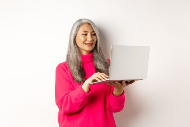 Femme asiatique senior travaillant à la pige à l'aide d'un ordinateur portable et souriante debout sur fond blanc