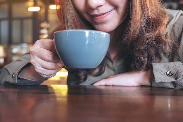 Femme asiatique sentant et buvant du café chaud avec se sentir bien au café