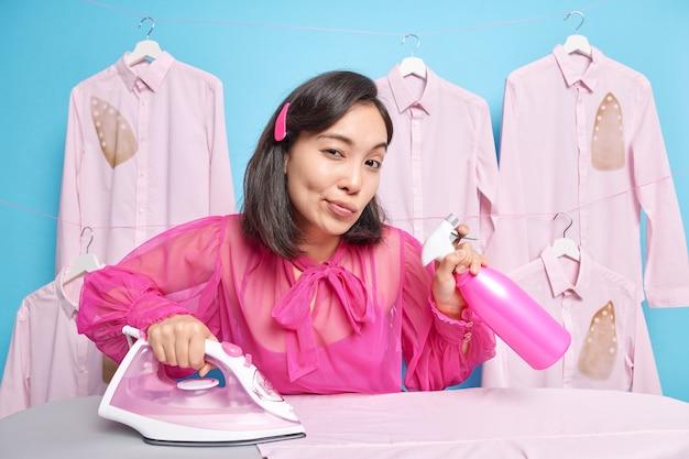 Une femme asiatique sérieuse aux cheveux noirs tient un jet d'eau pour rendre le tissu lisse regarde attentivement