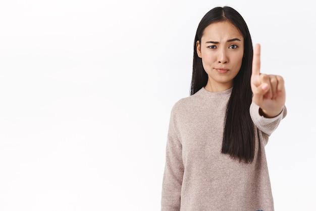Une femme asiatique sérieuse et confiante interdit et avertit un ami, demande l'arrêt, étire le doigt vers l'avant dans un tabou, geste de rejet, sourire narquois sceptique et mécontent, n'aime pas ce qui se passe