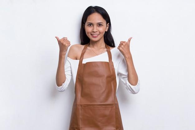 Femme asiatique serveuse barista portant un tablier avec signe ok geste tumb up isolé sur fond blanc