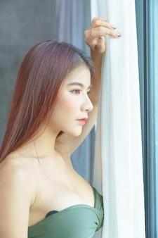 Femme asiatique sexy en bikini vert dans la chambre pendant les vacances