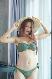 Femme asiatique sexy en bikini vert et porter un chapeau dans la chambre