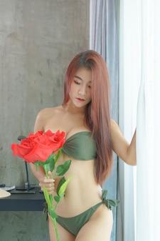 Femme asiatique sexy en bikini vert tenant une rose rouge sur la chambre