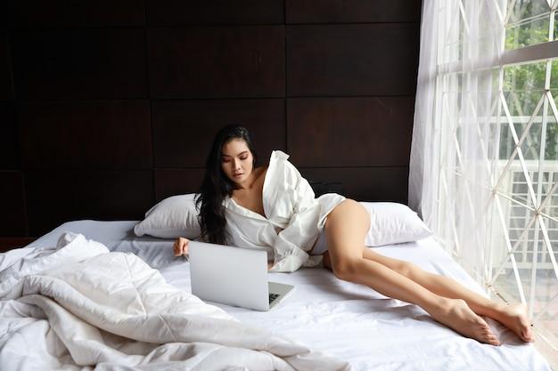 Femme asiatique sexy freelance adulte portant une robe blanche travaillant sur ordinateur en position couchée sur un lit dans la chambre