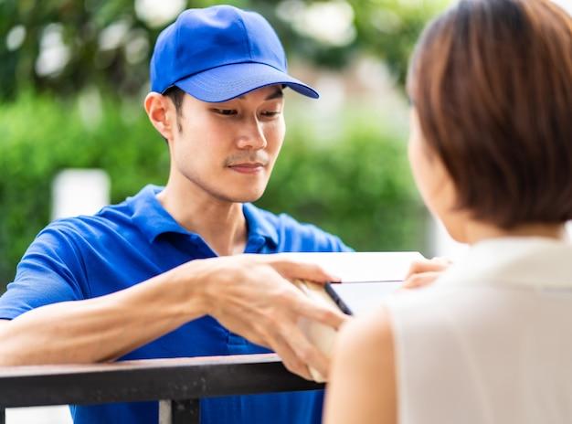 Femme asiatique signe une signature électronique à un appareil mobile portable après réception du colis