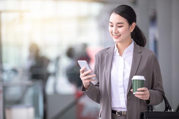 Femme asiatique avec smartphone debout contre le bâtiment flou de la rue. photo d'affaires de mode de belle fille dans une suite décontractée avec téléphone et tasse de café