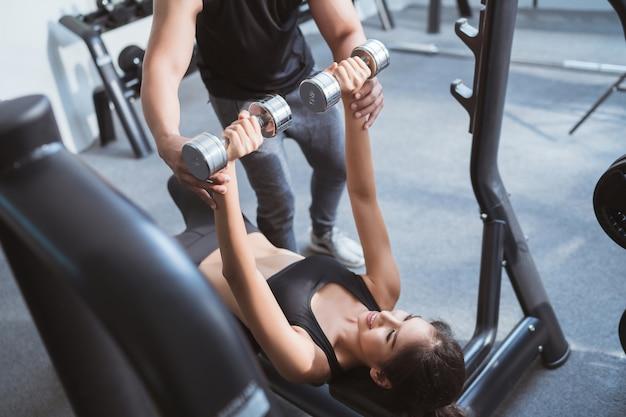 Femme asiatique, soulever, poids, les, supine, avoir, entraîneur personnel, peut, aider