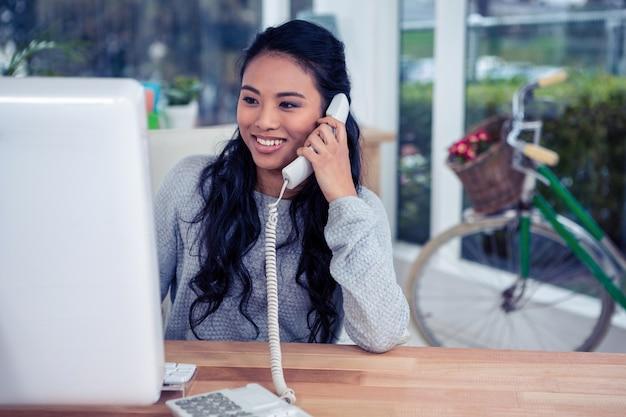 Femme asiatique souriante sur appel téléphonique au bureau