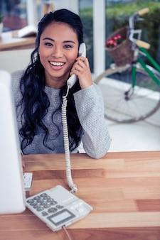 Femme asiatique souriante sur appel téléphonique en regardant la caméra au bureau